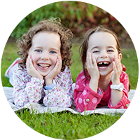twin-girls-laughing on the grass