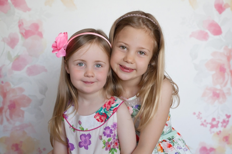two little sisters in floral dresses