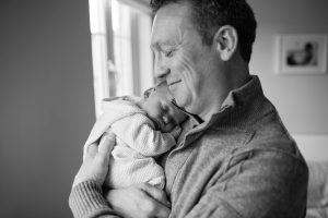 dad holding newborn baby black and white