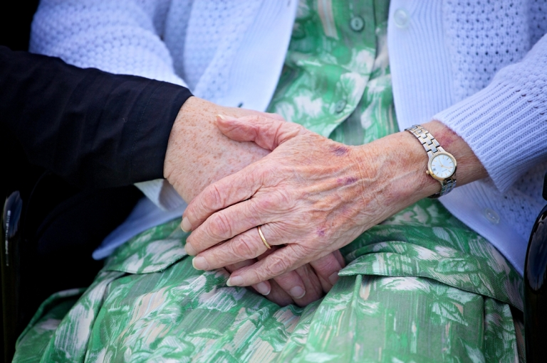women holding a hand of her elderly mother
