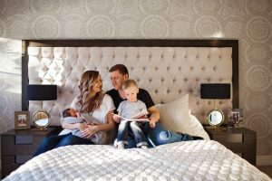 family with two kids sitting on the bed
