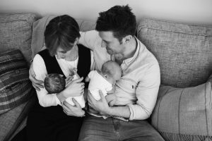 black and white image of parents holding their newborn twins