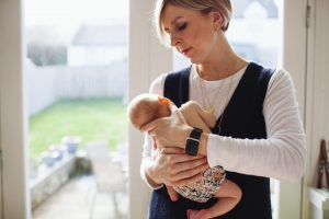 mum holding her newborn baby in front of a large window