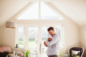 dad holding newborn son in front of large window