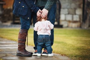 toddler girl standing at her parents feet