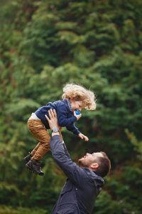 dad lifting his son in the air