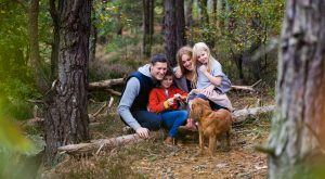 colour image of a family with young children and a dog in the forest