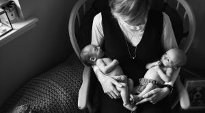 black and white picture of mum holding her newborn twins