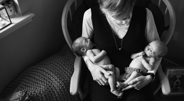 black and white photo of mum holding her newborn twins