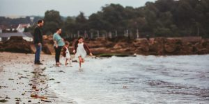 out of focus photograph of family on the beach in scotland