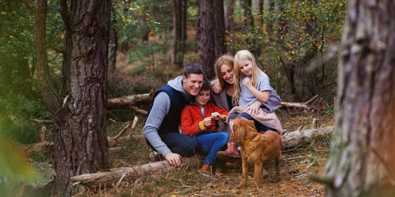 beautiful family with a dog in the forest in Scotland