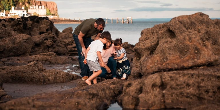 family with two small children looking for shells on the beach in Scotland