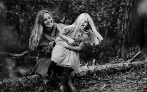 Beautiful mum and daughter in the forest laughing