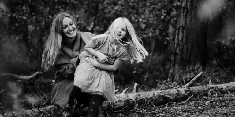 black and white photograph of mum and daughter in the forest