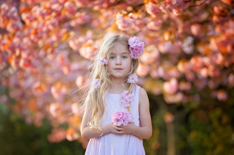 young girl with tree in blossom behind her