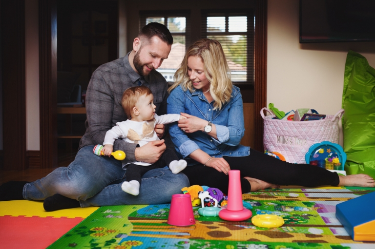 family with a small baby girl playing on the floor
