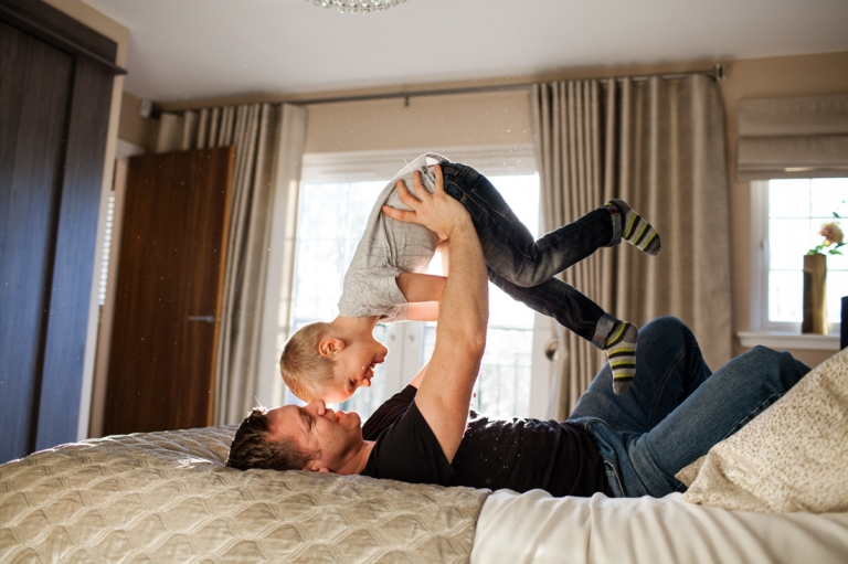 dad holding his son ubove himslef on a bed