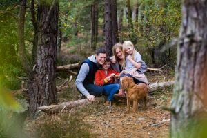 family with a spaniel in the forest