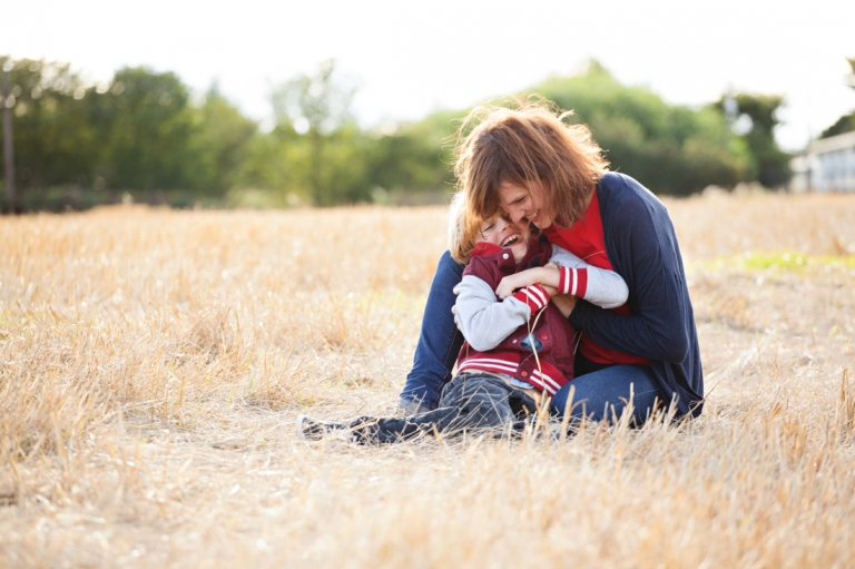 mum with son sitting on the dry grass
