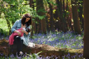new mum breastfeeding her baby in the woods