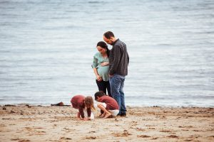 family expecting third baby playing on the beach