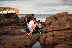 family collecting shells on the Scottish beach