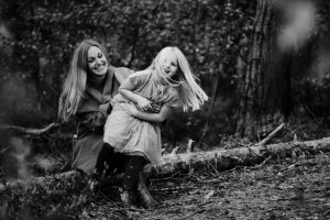 black and white photo of a beautiful mum in the forest with her daughter playing