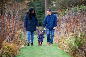baby girl walking holding hands of her parents